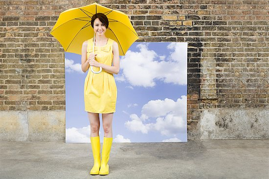 6114-06596532 © Masterfile Royalty-Free Model Release: Yes Property Release: Yes Young woman with umbrella and sky background