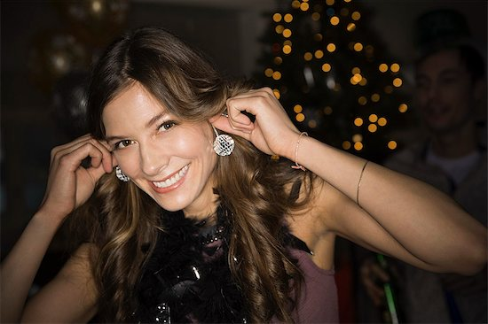 6117-07361520 © Masterfile Royalty-Free Model Release: Yes Property Release: Yes Woman using mini disco balls as earrings during New Years Eve party