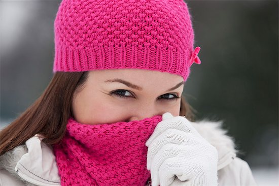 639-06043153 © Masterfile Royalty-Free Model Release: Yes Property Release: No A young woman wearing a pink hat and scarf, trying to keep warm