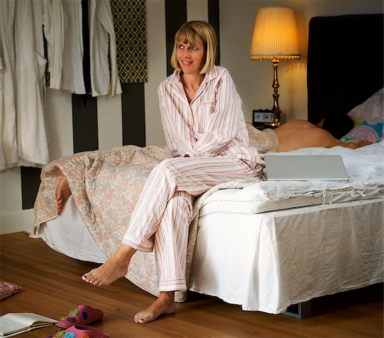 869-05969372 © CulturaRM / Masterfile Model Release: Yes Property Release: No Mature woman sitting on bed in pyjamas